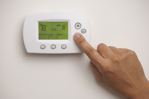 A person using a thermostat