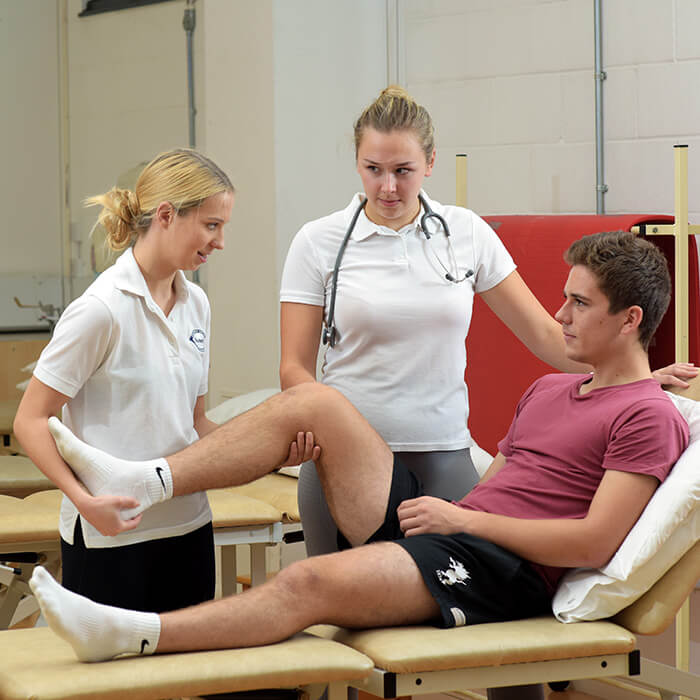 female physiotherapy student performing treatment on male patient knee with another female in the background