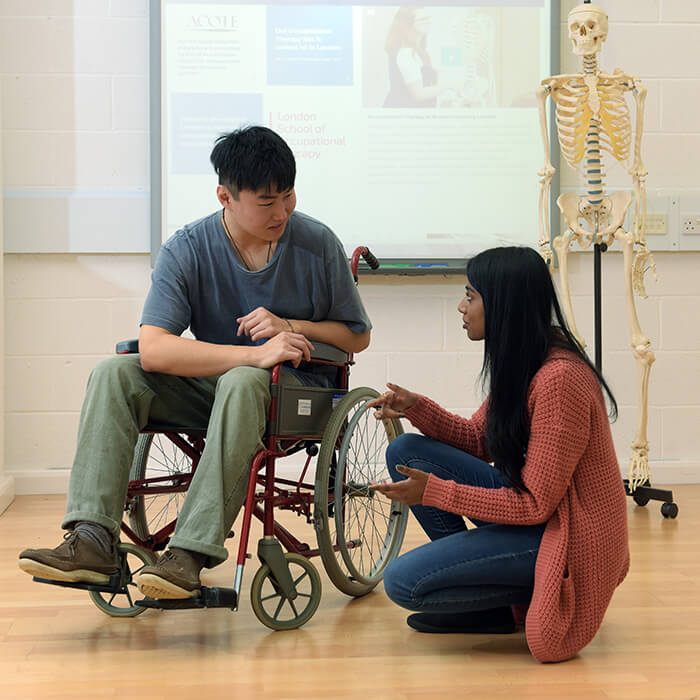 female student talking to a young man in a wheelchair