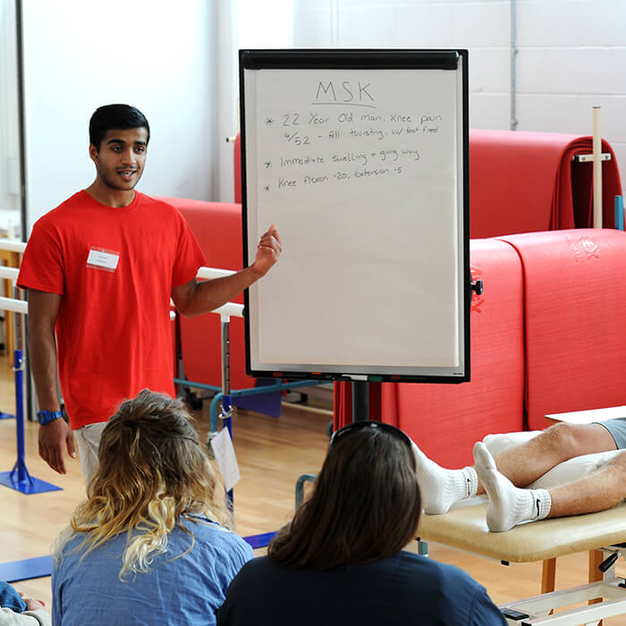 male physiotherapy student explaining case study on a board