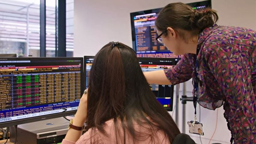 Business-students-looking-at-stocks-and-shares-on-computer-screens