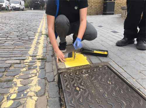 Environment agency worker stencilling a fish on the pavement as part of the yellow fish campaign