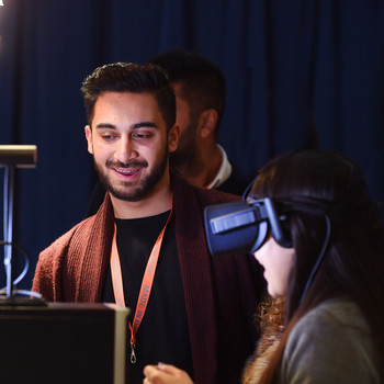 Computer science student showing his final year project, a 360 virtual reality experience to visitor