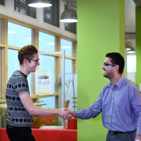 An Economics and Finance student shakes a staff member's hand at the Professional Development Centre