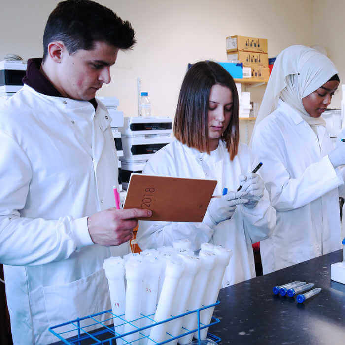 one male and two female Environmental Sciences students doing water sampling in a laboratory at Brunel University London