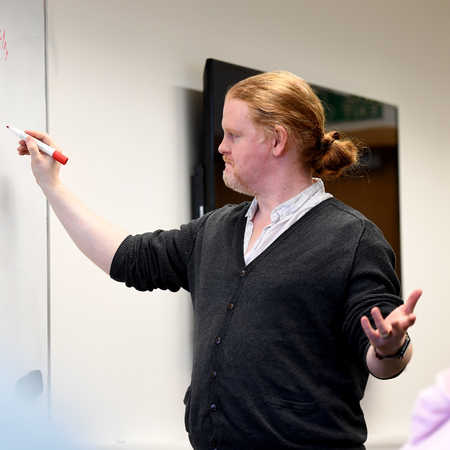 Brunel Univeristy London Games design lecturer writing on whiteboard and presenting to class