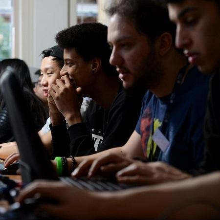 a-row-of-male-games-design-students-sitting-smiling-and-staring-at-their-computer-screens