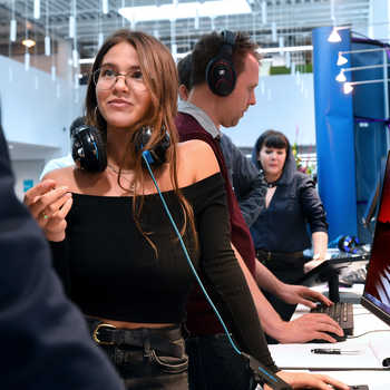 female-games-design-student-in-the-foreground-wearing headphones