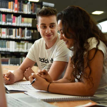 smiling-male-and-female-students-studying-in-a-library