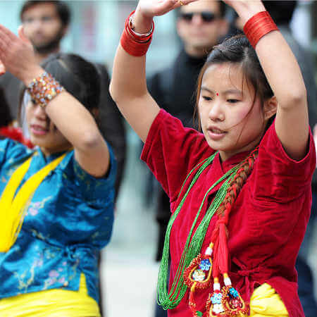 Chinese students dancing in traditional native costumes.