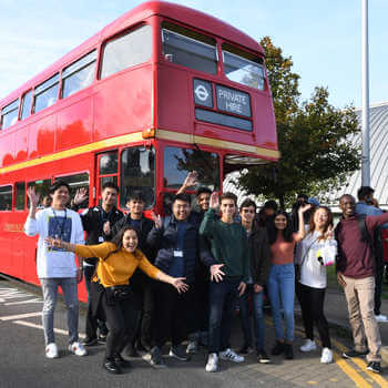 Brunel students going on a trip and standing in front of a red London bus.