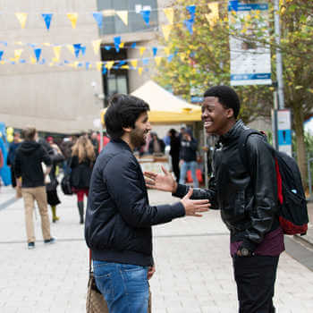 two students smiling and greeting each other with a handshake on brunel campus