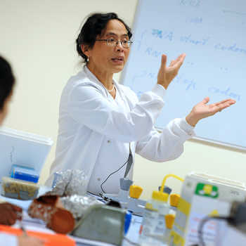 female lecturer in a white coat teaching in a laboratory at Brunel University London