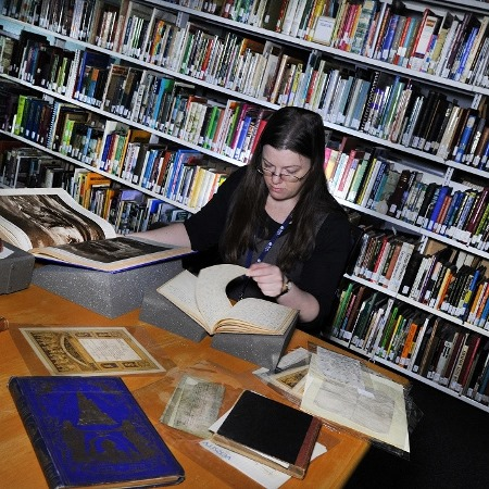 A reader at a table of Special Collections material