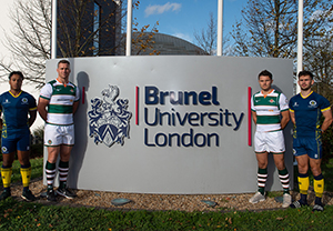 Brunel University and Ealing Trailfinder rugby players in front ot the university logo
