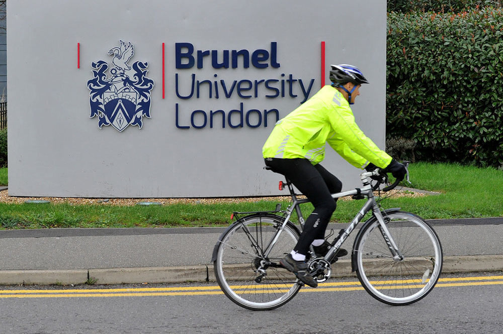 Cyclist passing Brunel sign