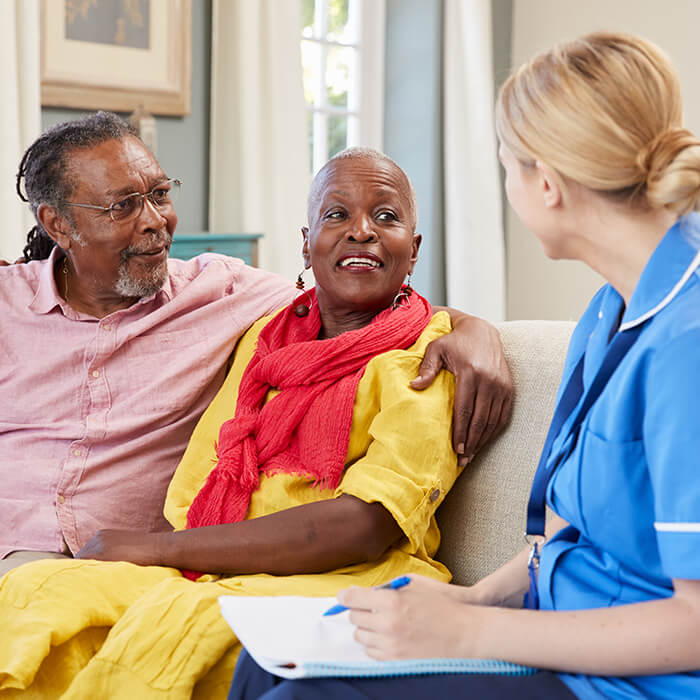 healthcare professional talking to elderly couple