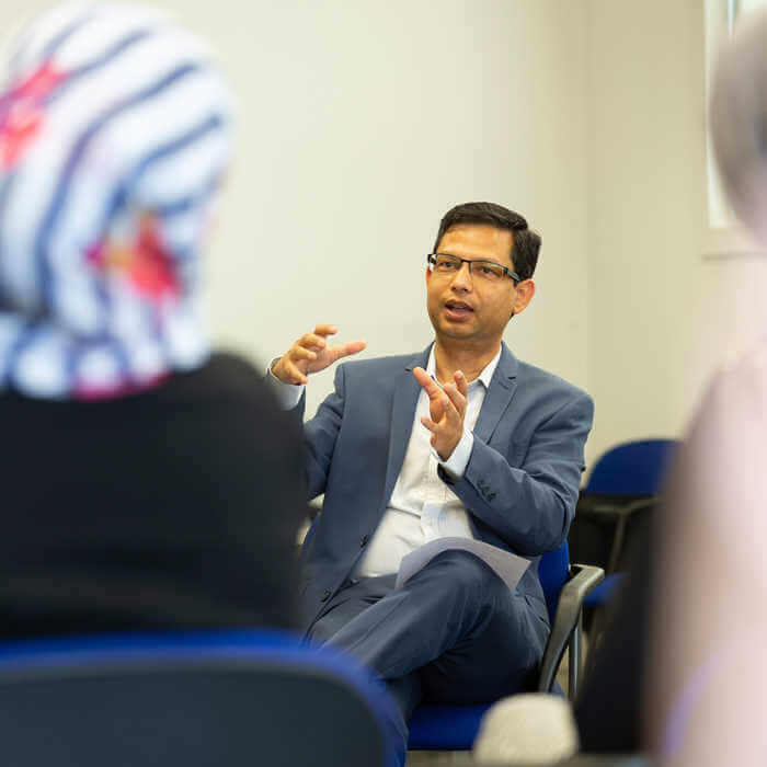 male lecturer talking to students in a classroom