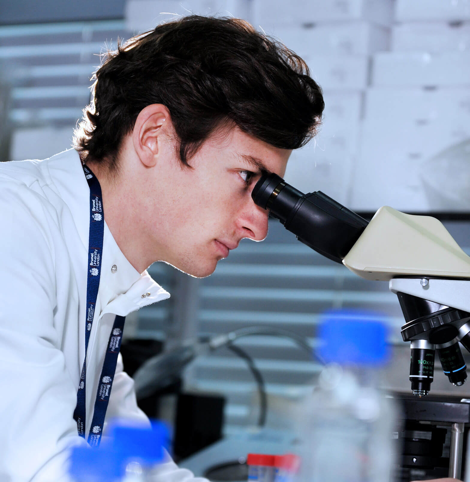 Male student looking through microscope in a bioscience lab