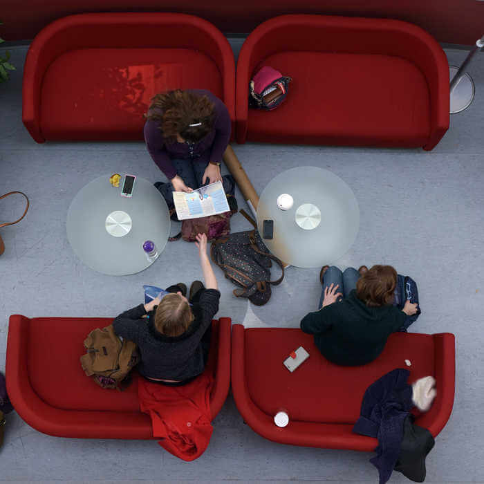 3 students studying together on red armchairs