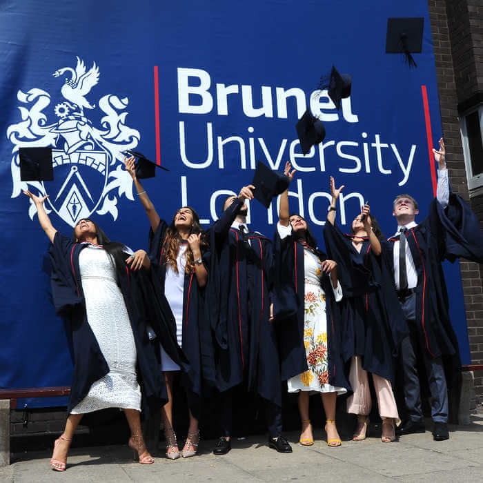 group of graduating students in front of a large Brunel University sign(1)