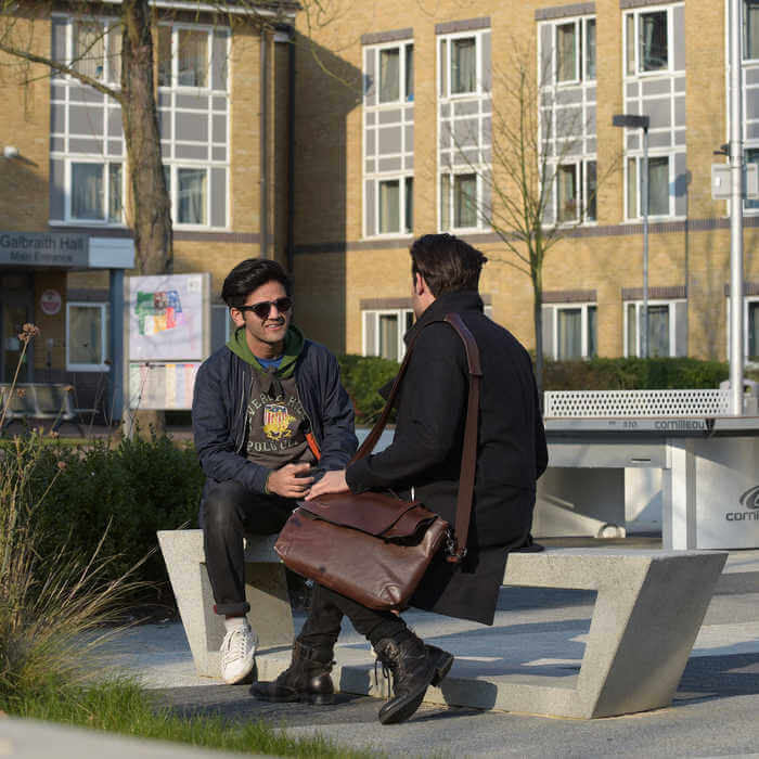 two students chatting on a bench 1