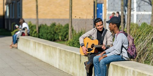 Students chilling on campus with a guitar