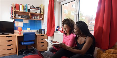 Students studying in their Brunel accommodation room