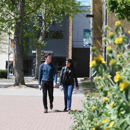 Two students walking along Brunel's campus