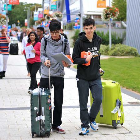 two new students walking across campus with their suitcases