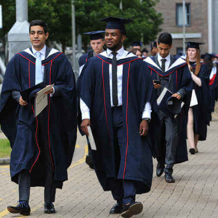 brunel graduates walking down concourse with graduation gowns