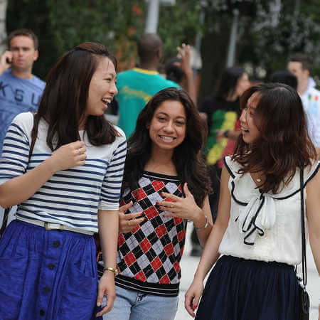 postgraduate study international students walking through campus smiling and laughing